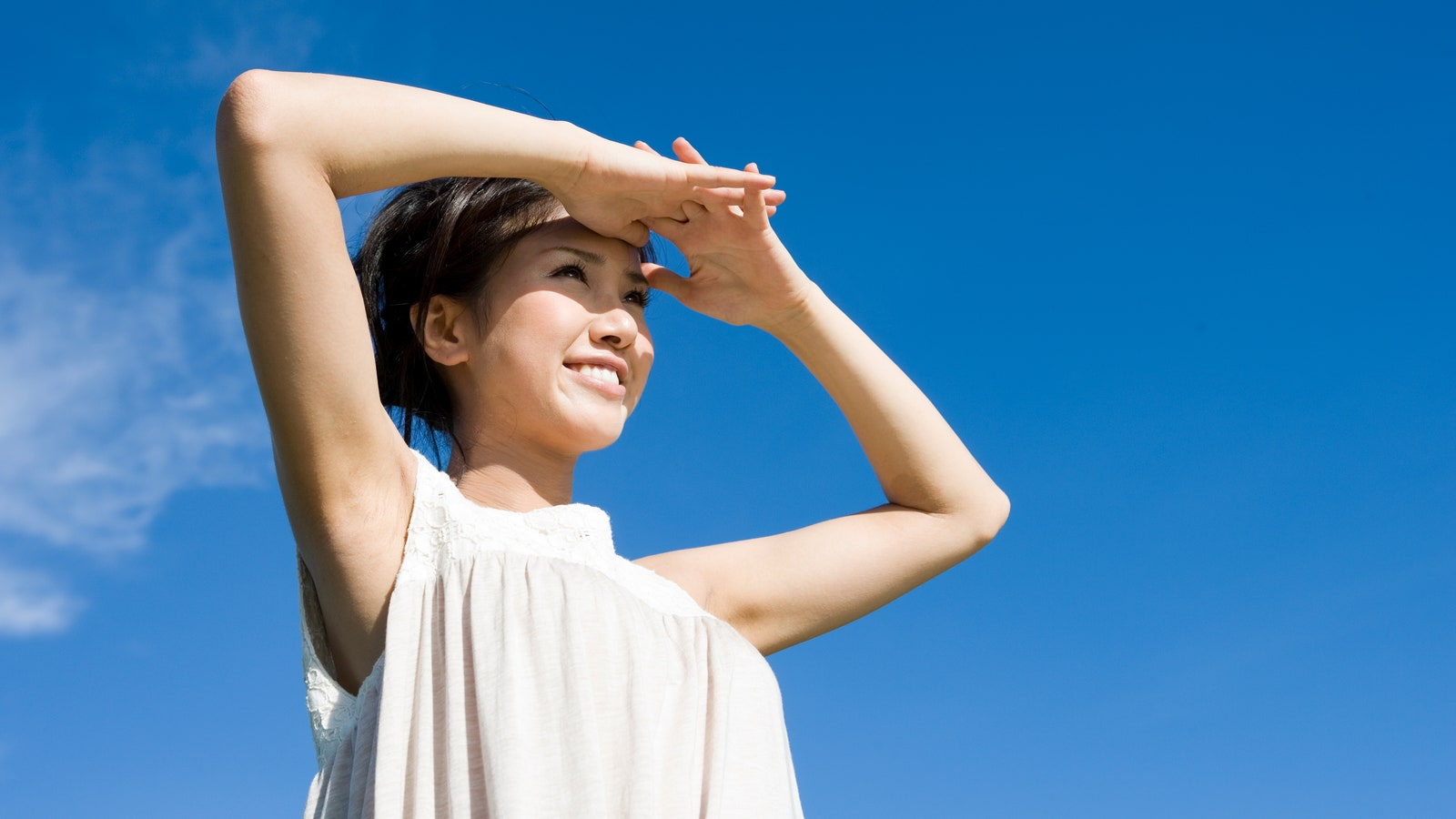 A woman with raised arms shielding her eyes from the sun against a clear blue sky