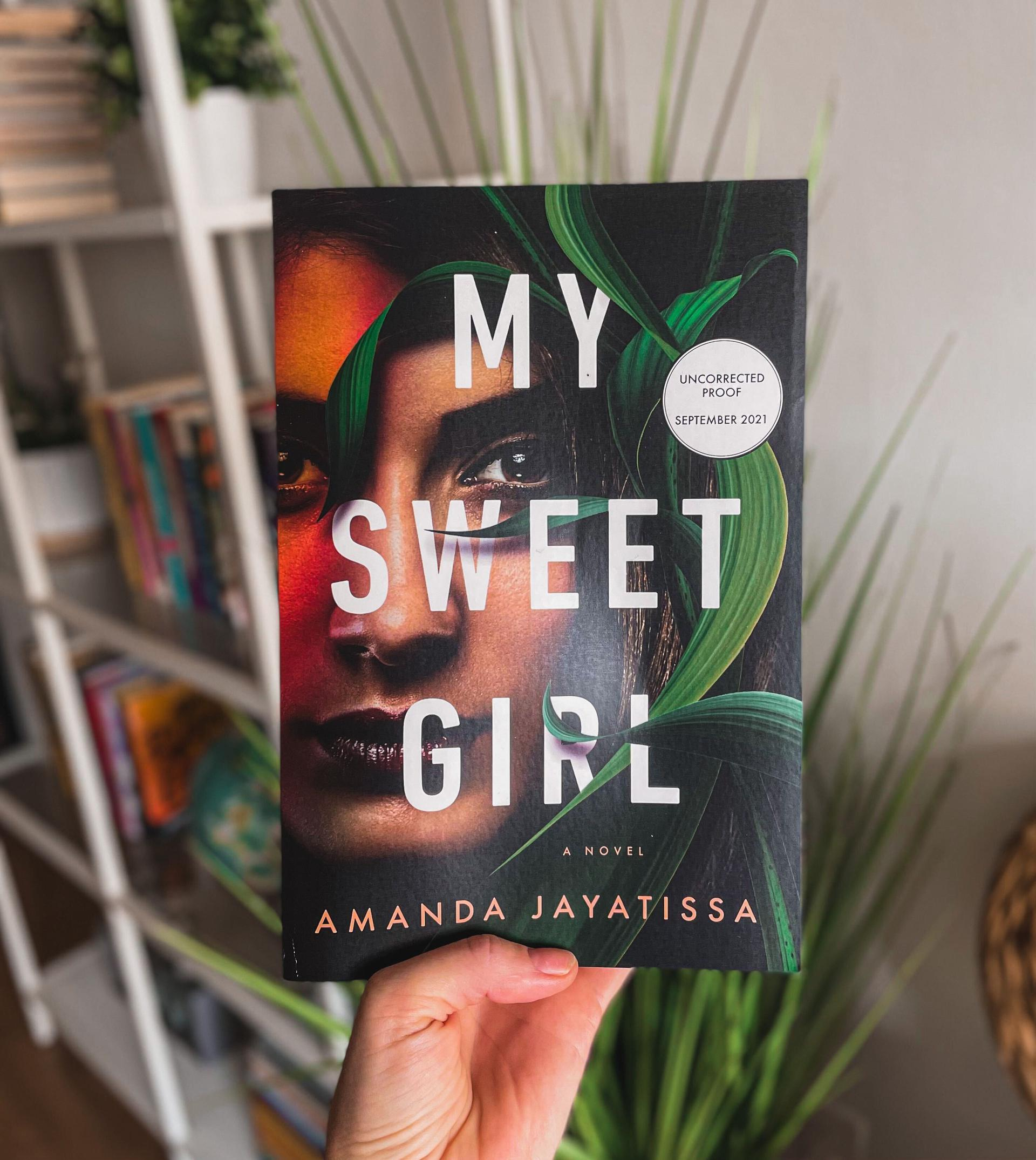 a hand holds a copy of ''my sweet girl'' against a backdrop of a plant and bookcase