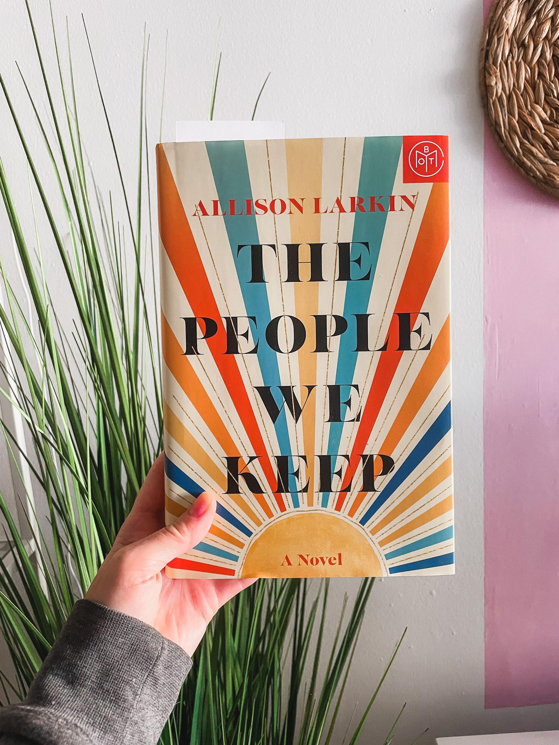 a hand holds a copy of the book against a blank wall next to a spiky plant