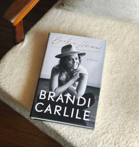 Book ''Broken Horses: A Memoir'' by Brandi Carlile on a plush chair cushion