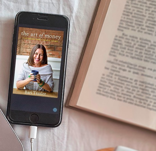 An iPhone showing ''The Art of Money'' by Bari Tessler on the screen is on top of a blanket, next to an open book with blurred text