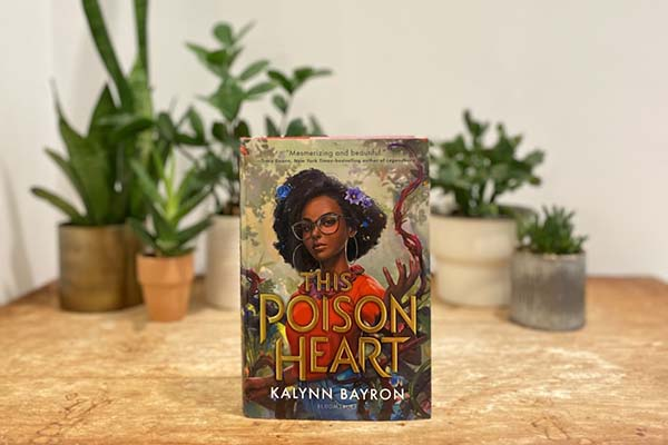 ''This Poison Heart'' stands upright in the foreground; in the background, blurry potted plants