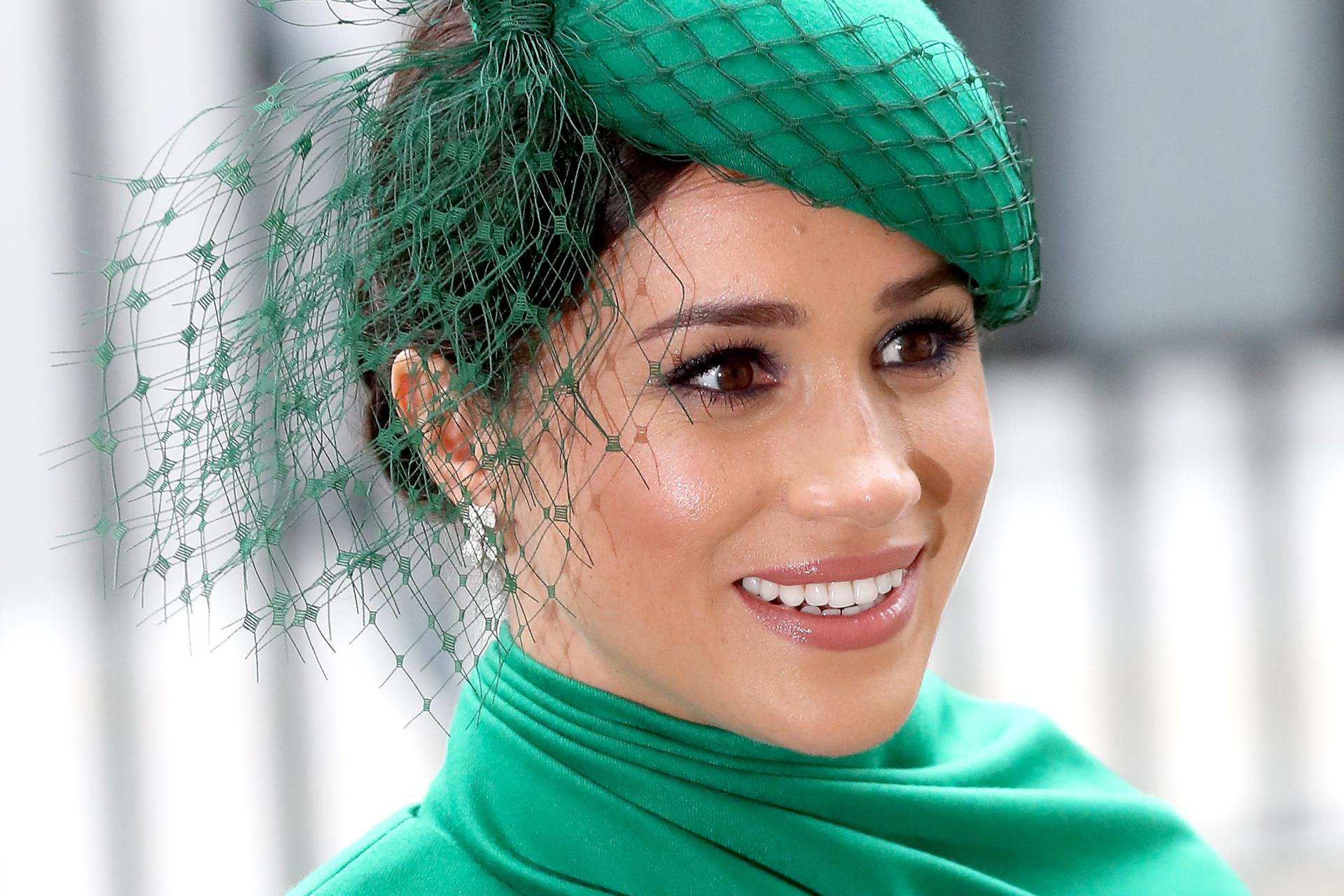 Meghan Markle smiles in an elaborate netted hat