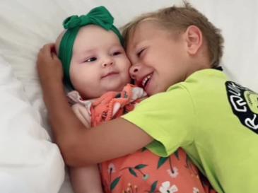 boy cuddling baby sister