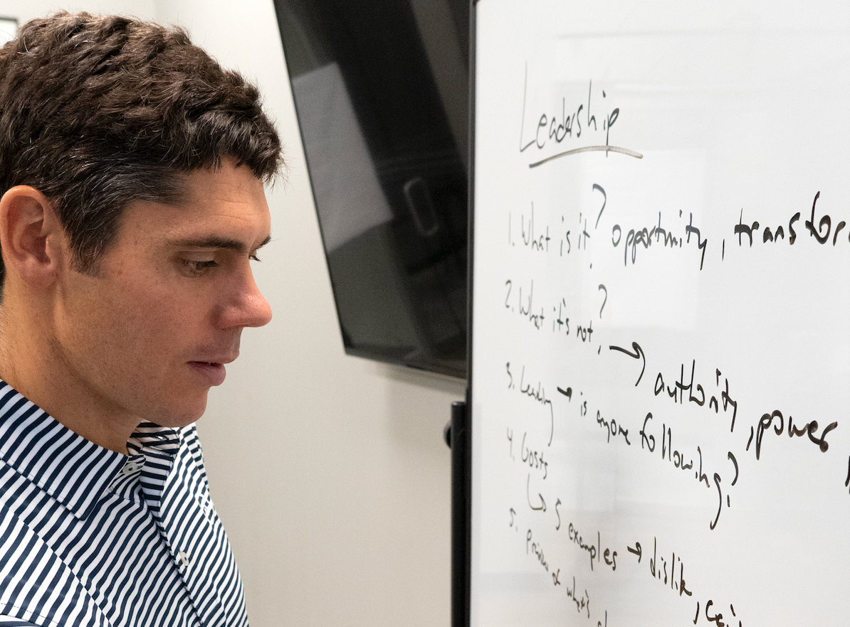 man looking at white board in class