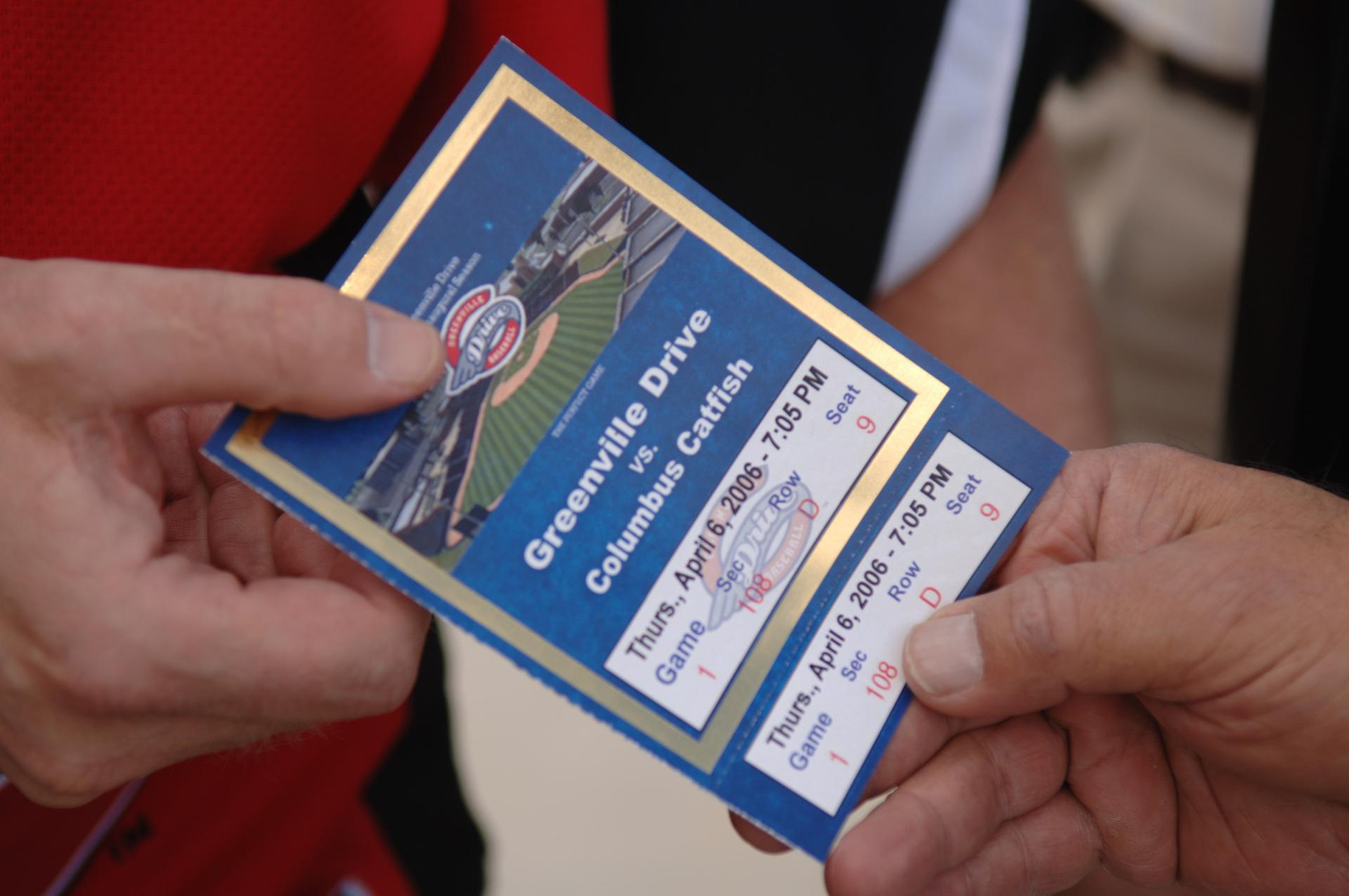 Paper ticket with date, game, and seat information changing hands