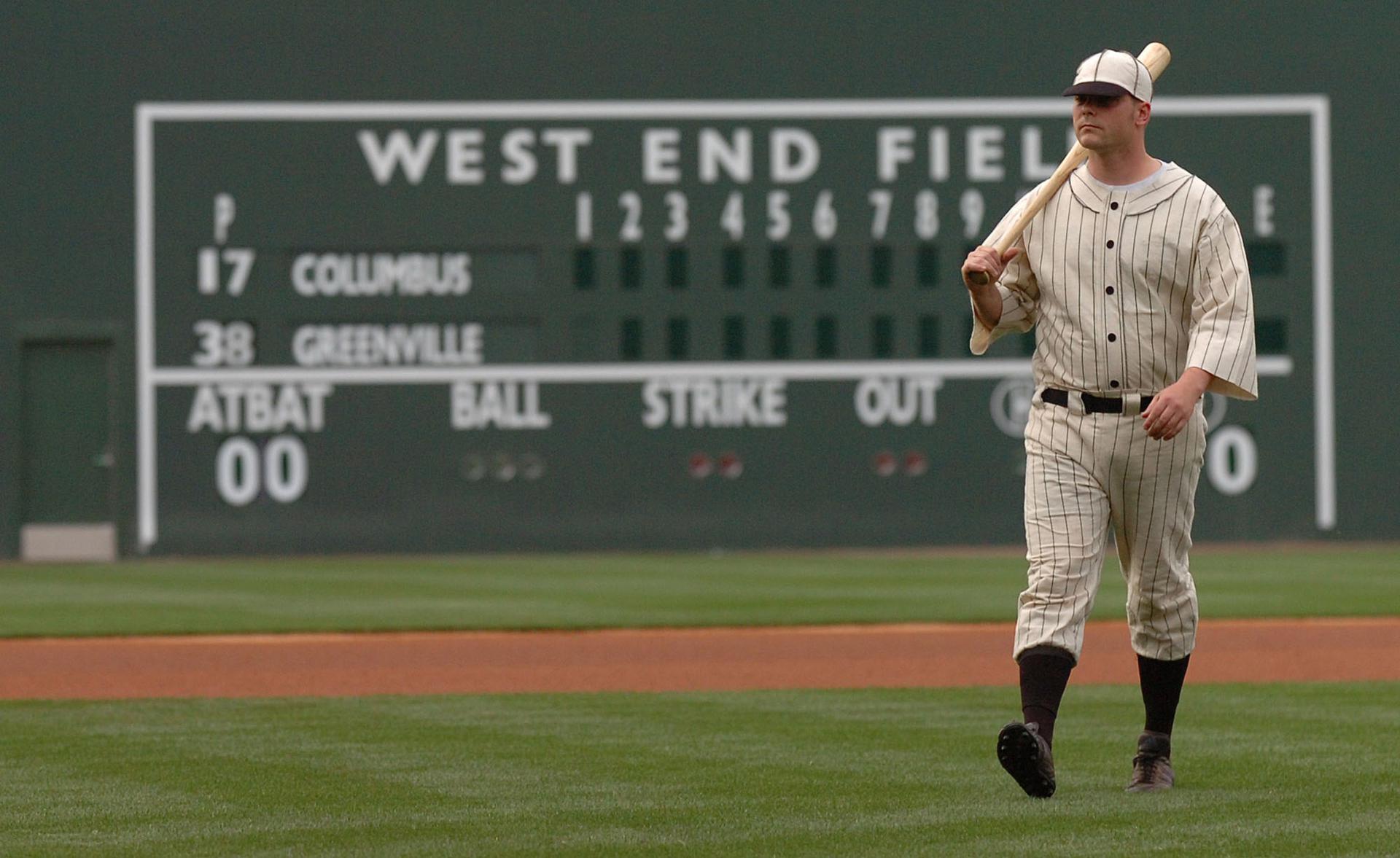 A man dressed in an old-fashioned baseball uniform holding bat walks across field