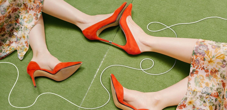 feet in red high heels against a mirror