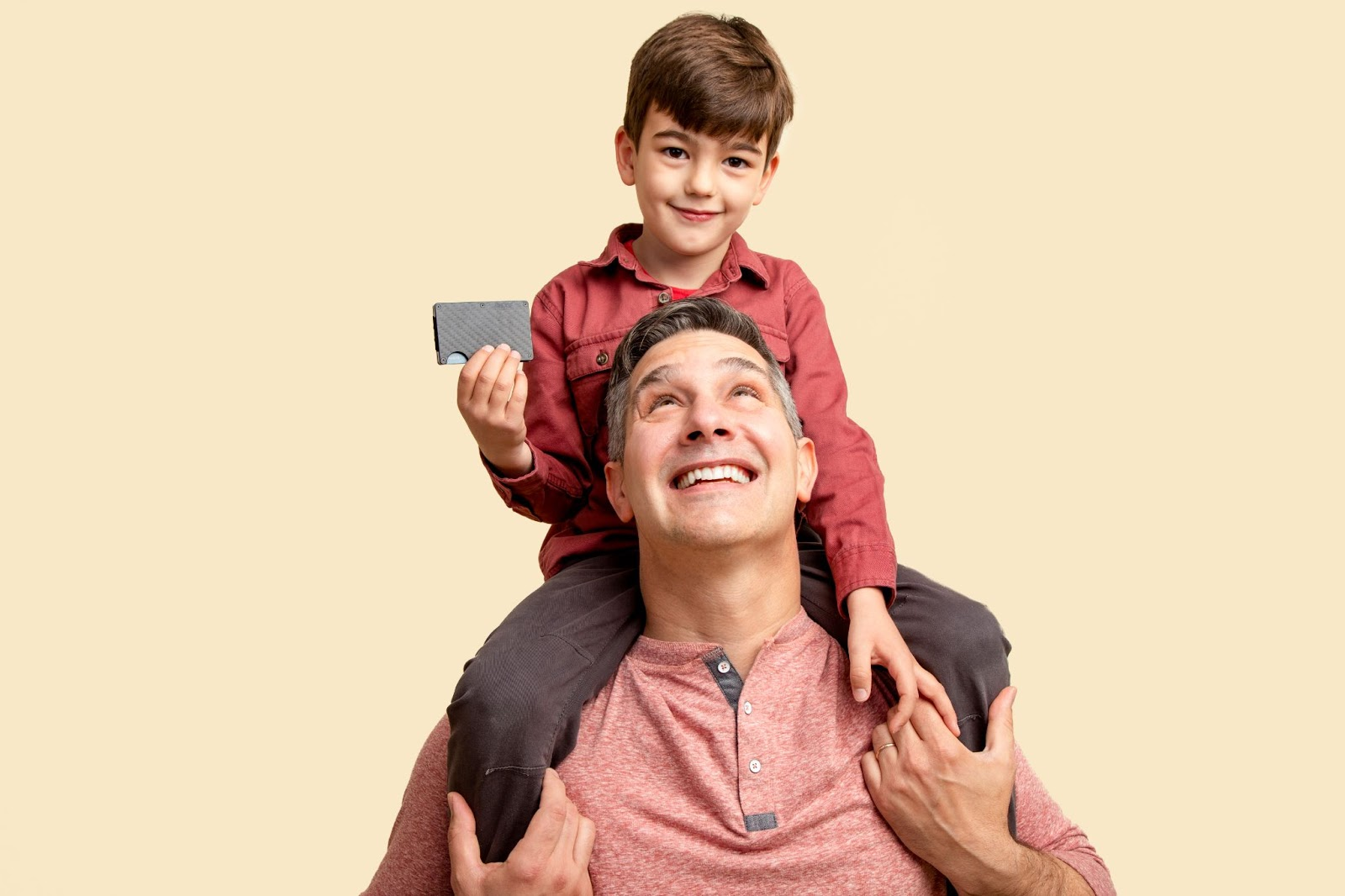 Photo of a child on his dad's shoulders, holding a wallet