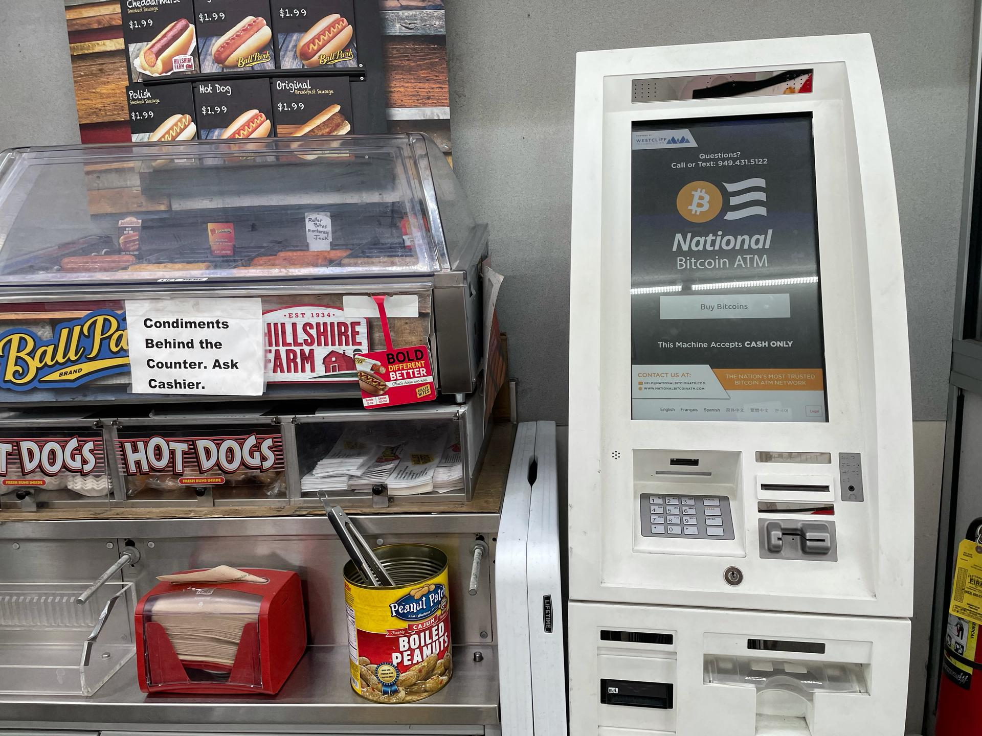 Photo of an ATM machine displaying the words ''National Bitcoin ATM,'' located in a gas station next to a hot dog stand.