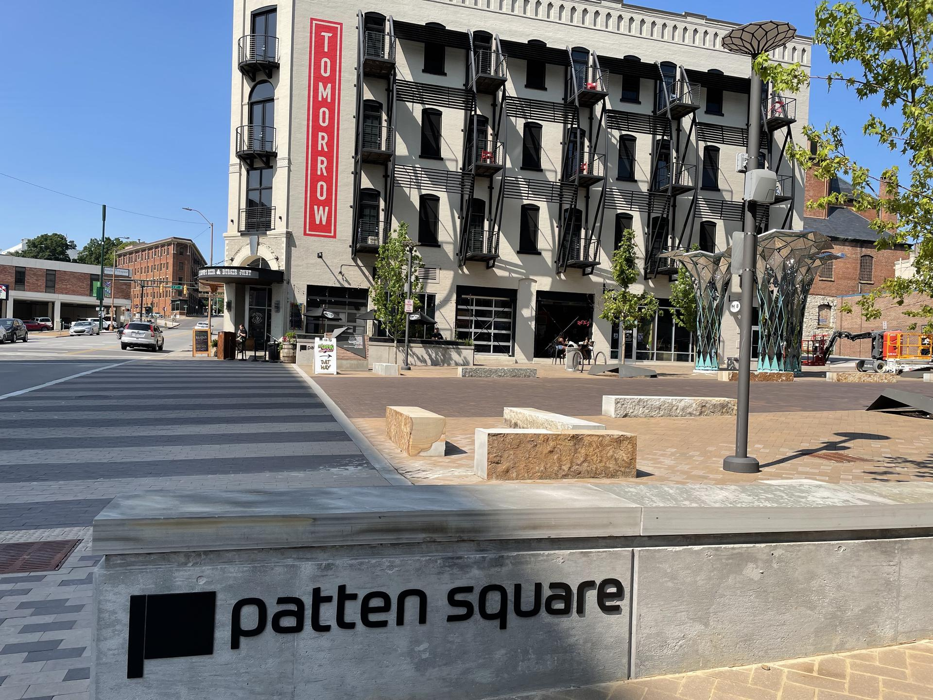 Photo of a stone bench that reads ''Patten Square'' on the side, pictured in front of a street with a large apartment complex on the other side.