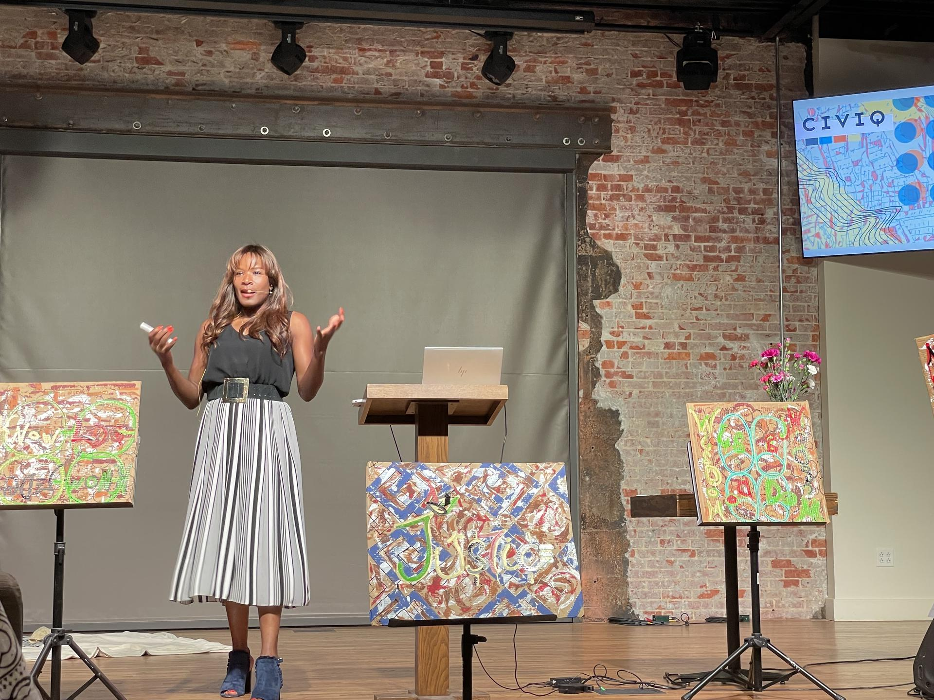 Photo of a woman standing on a stage and speaking. There are 3 painted canvases on stage with her, 2 to the right of her and 1 to the left.