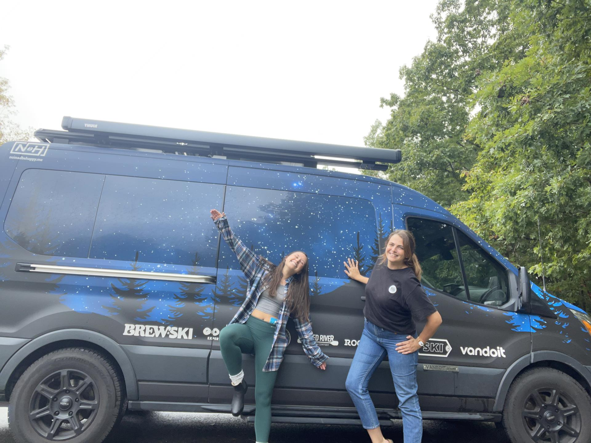 Photo of Trista and Brianna standing in front of a van that features the image of a night sky with stars and dark trees.