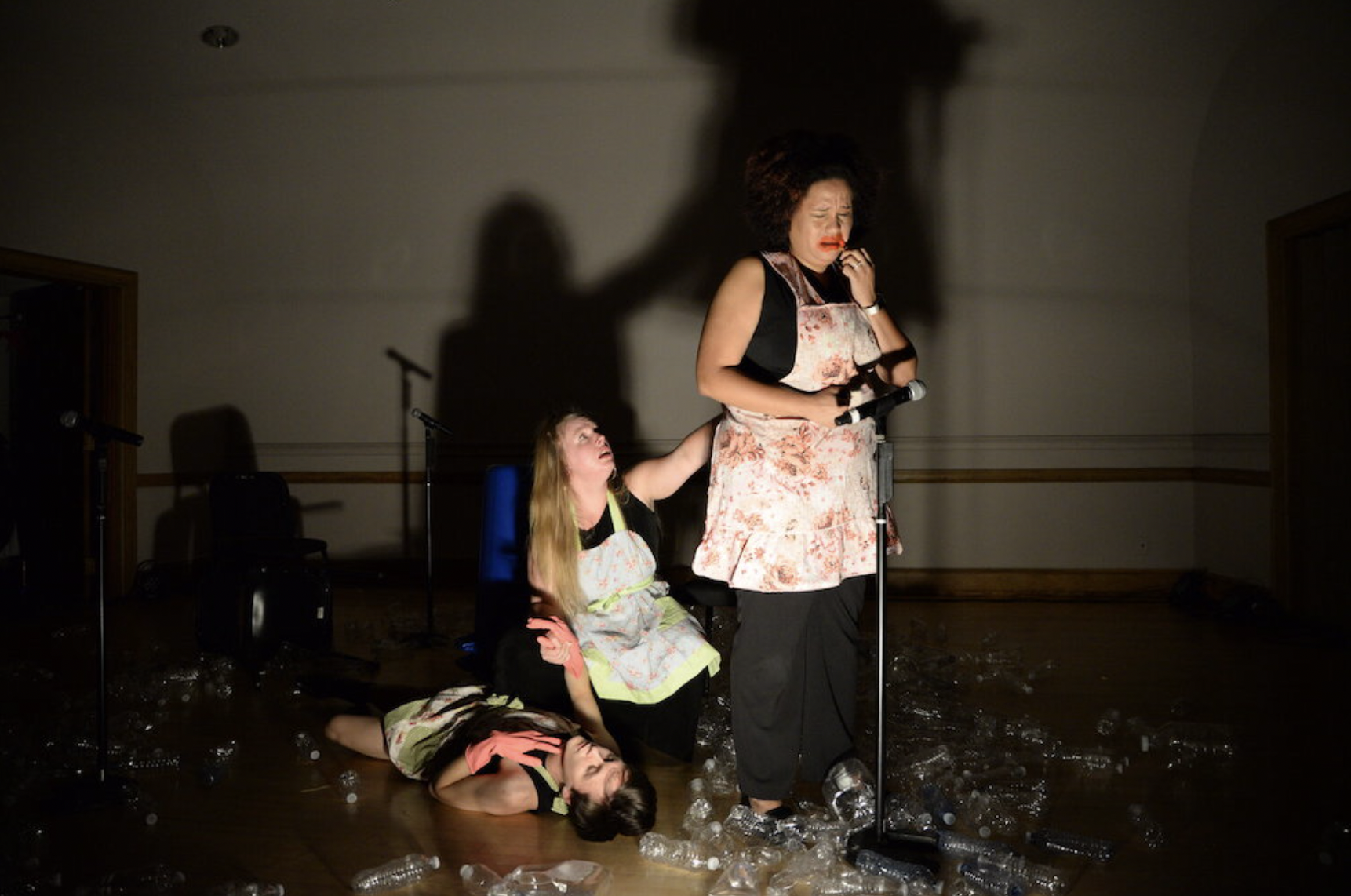 Photo of three actors on a dark stage with a mic in front of them. One of the actors is crying, one is reaching out to her, and the other is lying on the ground.