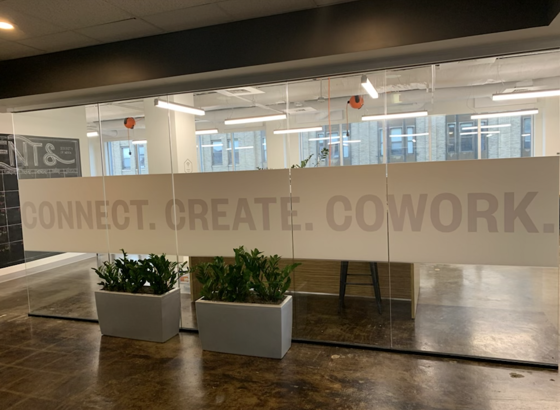 Photo of an office space with a large glass screen that reads ''Connect.Create.Cowork.''