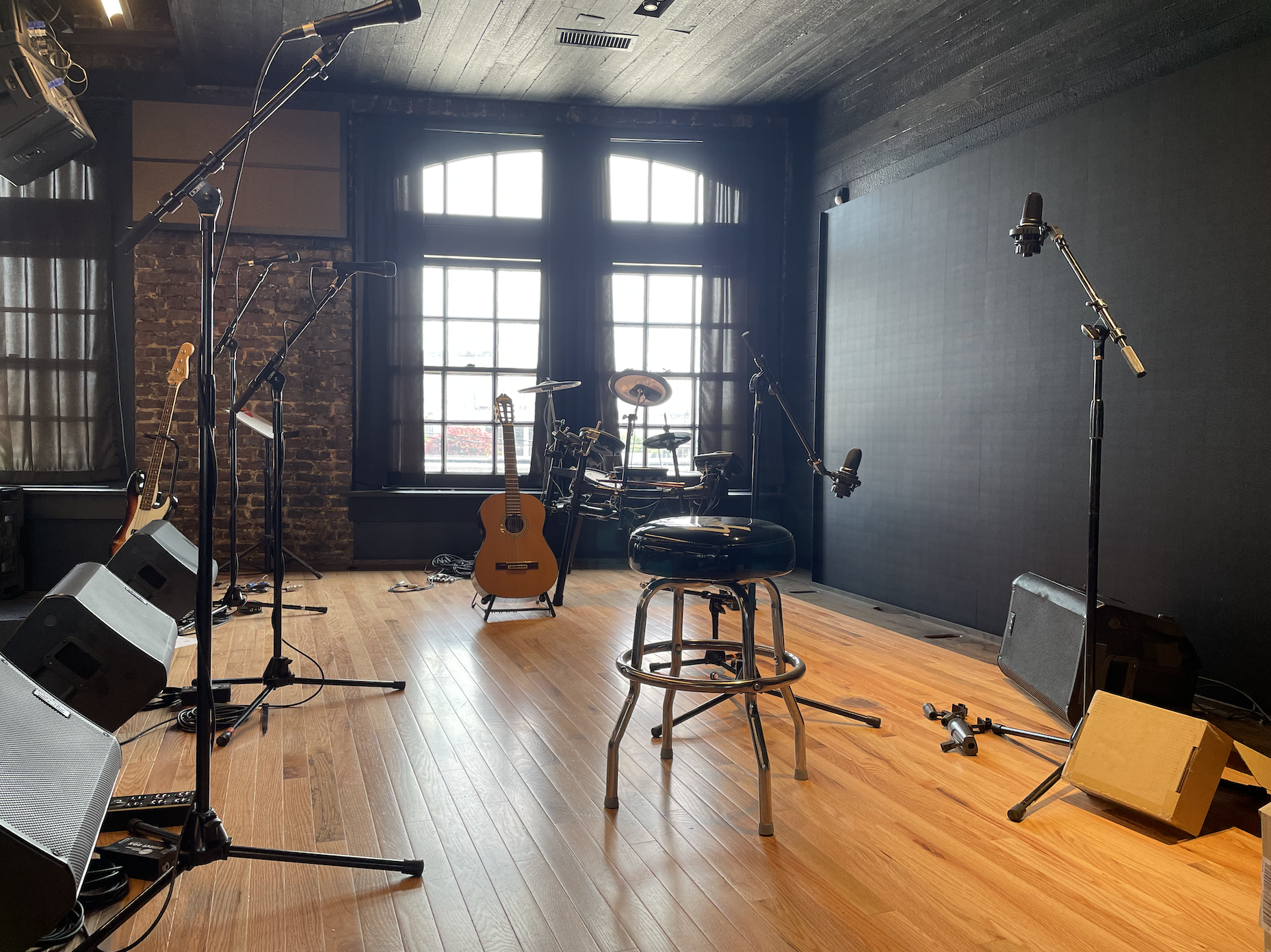 Photo of a wooden stage with a stool, drum set, guitar, and several mics + amps scattered across it.