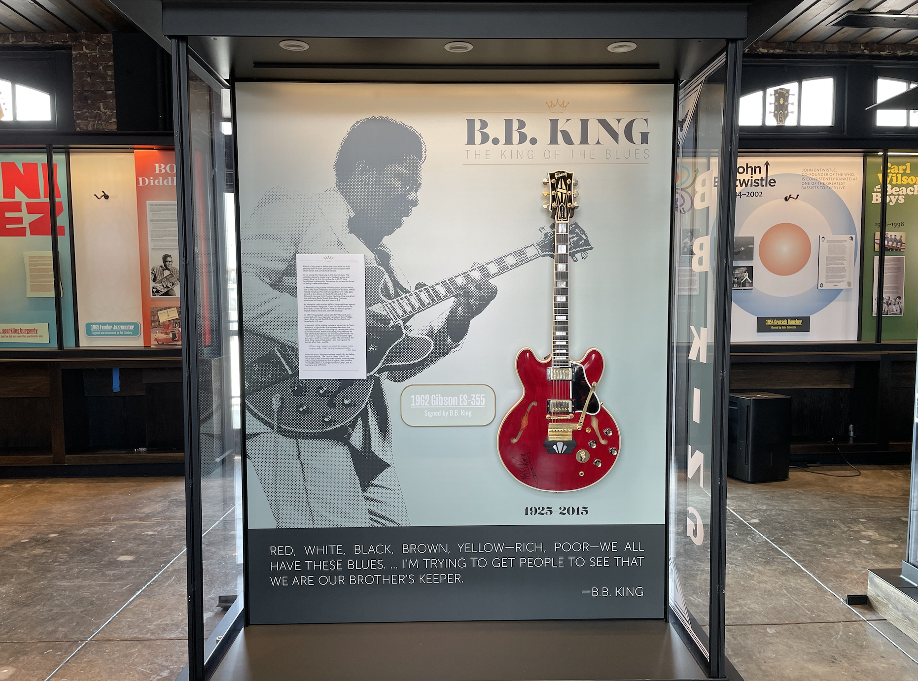 Photo of a glass display case showing an image of BB King and the words ''BB King'' displayed prominently. The display case also features a red electric guitar.