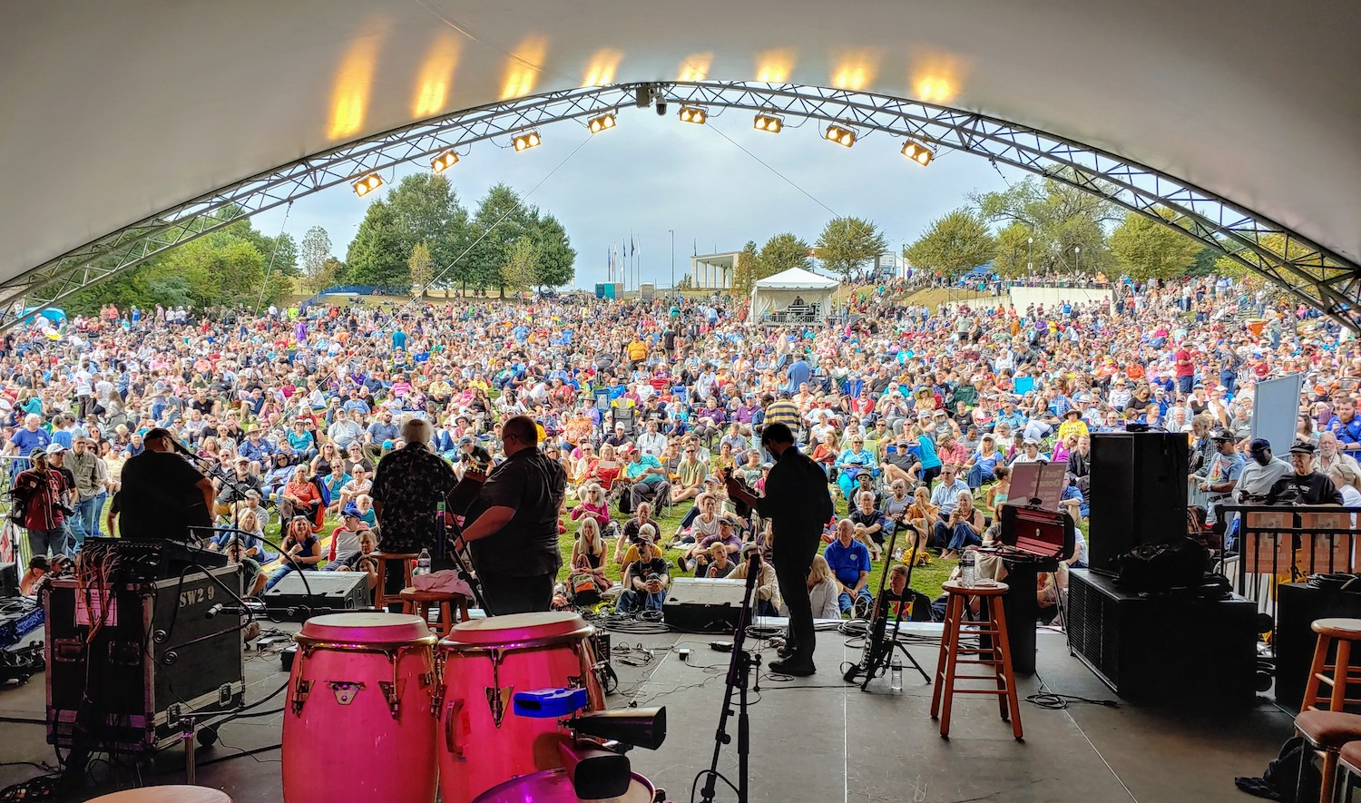 A view of the crowd at a past folk festival from the back of the stage. People playing instruments are shadows in the foreground.