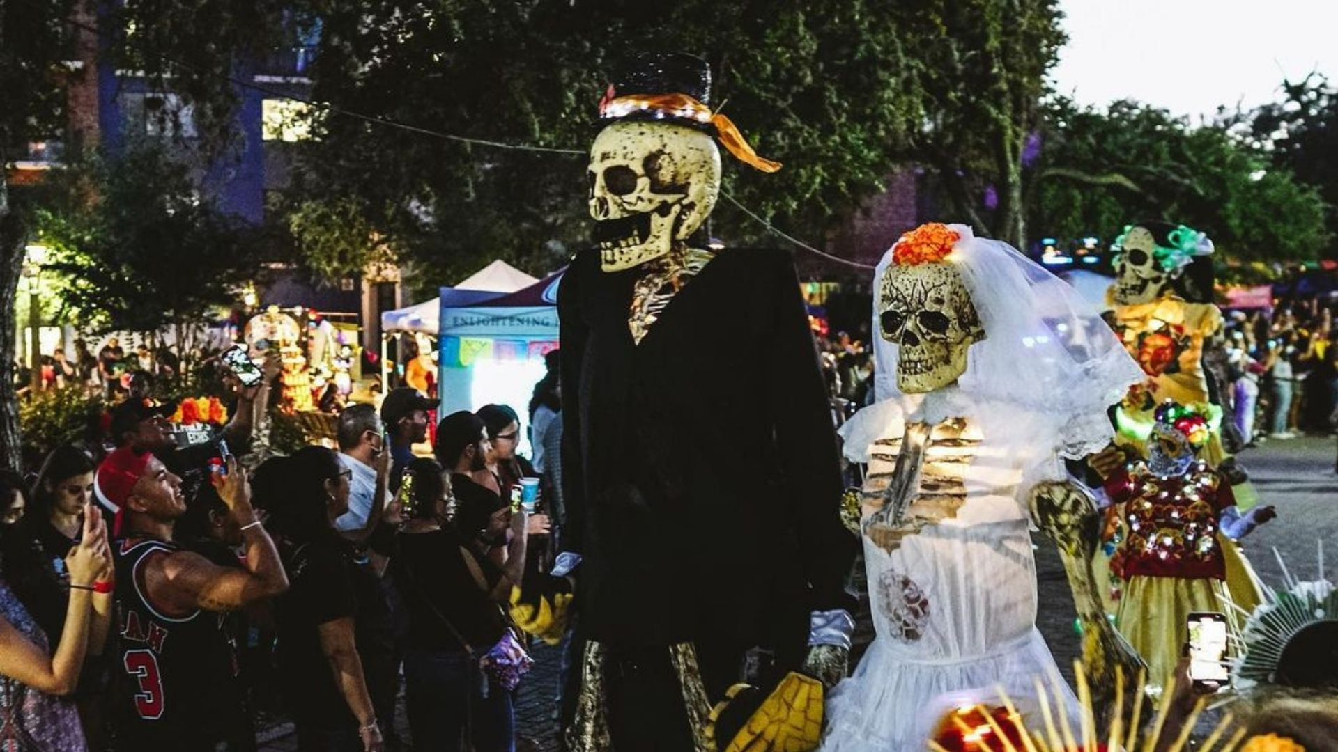 Pictured is a parade of 10-foot-tall skeleton puppets in a procession down a lined-up crowd.